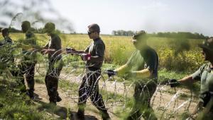 Węgierscy żołnierze rozkładają drut kolczasty wzdłuż granicy z Chorwacją. 18.09.2015