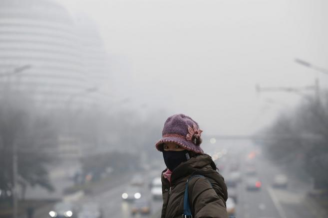 Pekin, Chiny, 24 lutego 2014 roku. Kobieta w ochronnej maseczce na twarzy przechodzi przez kładkę dla pieszych, EPA/ROLEX DELA PENA Dostawca: PAP/EPA.
