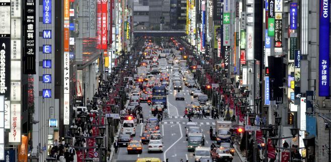 Główna ulica dzielnicy Ginza w Tokio zapełniona przechodniami.